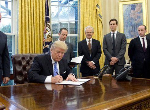 Trump tekent Global Gag Rule omringd door mannen: een parodie